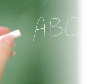 someone writting ABC on a green chalkboard